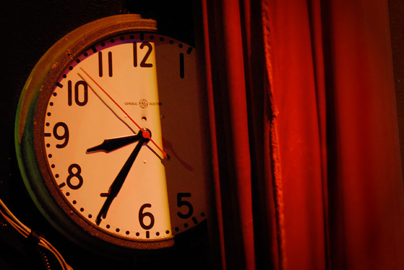 A General Electric analogue clock face side stage and partly obscured by a red curtain reads 8:35 at Portland, Oregon's Aladdin Theater.