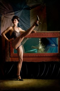 In front of a striped circus tent, a white or mixed race, brunette showgirl wearing a black top hat and fishnets kicks high in the air as she leans upon a victorian, steampunk water tank containing a red haired mermaid wearing pearls.
