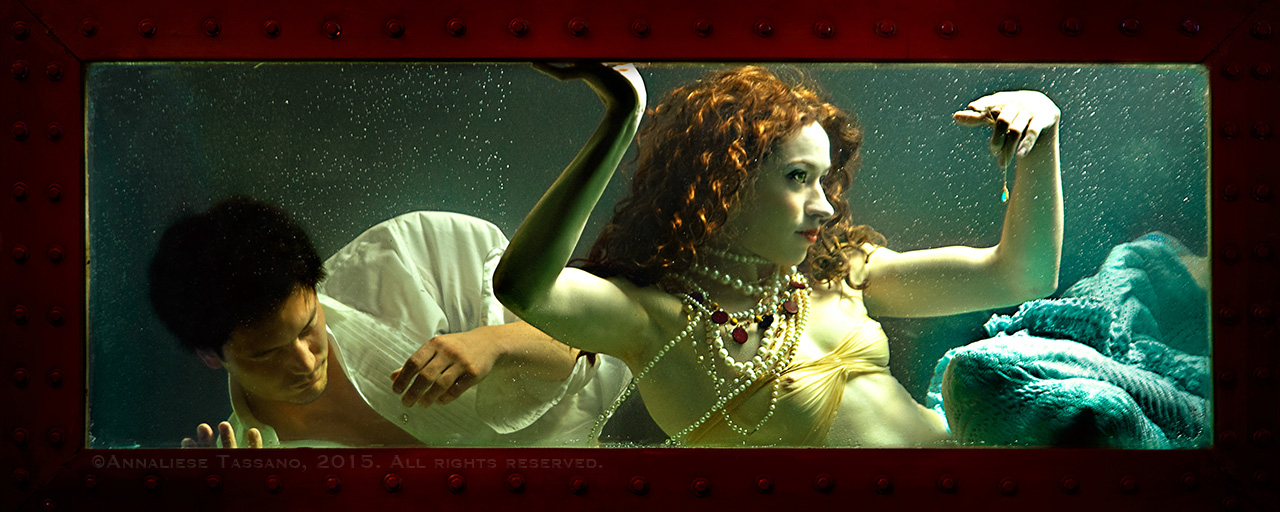 A red haired mermaid in a tank with a dead man behind her.