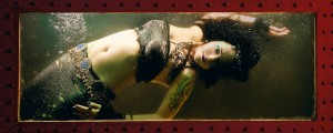 A tattooed, white mermaid with black hair and heavy silver jewelry floats in a bubble filled tank of water.