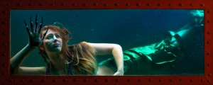 Green tailed mermaid claws the window of the tank in which she is imprisoned.