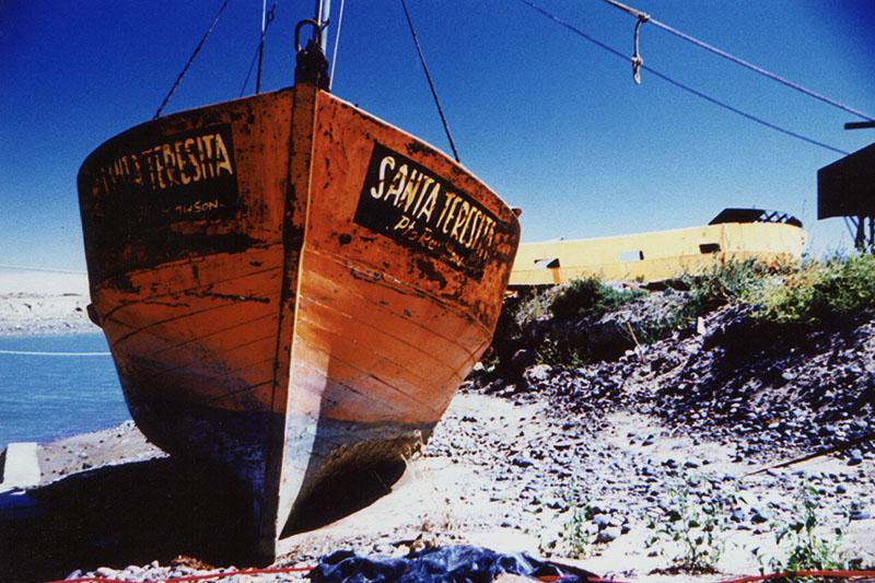 The fishing boat Santa Teresita sits on dry land at a boatyard outside Puerto Madryn, Argentina. Cross Process.