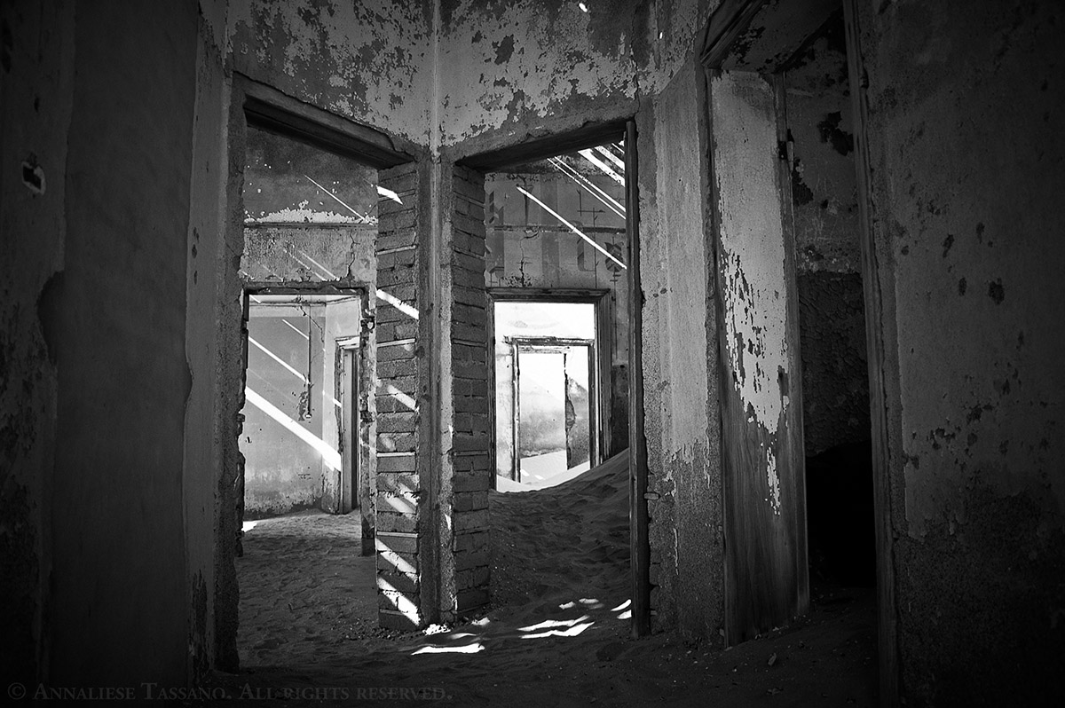 A black and white view of many doors in one of the many sand filled buildings found in Kolmanskop, once a thriving diamond mining community in the Namib Desert of Namibia.