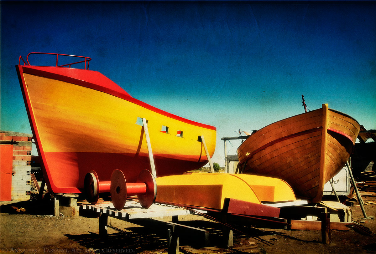 A boat yard near Puerto Madryn, Argentian, filled with wooden boats painted bright colors such as red, yellow, and orange.