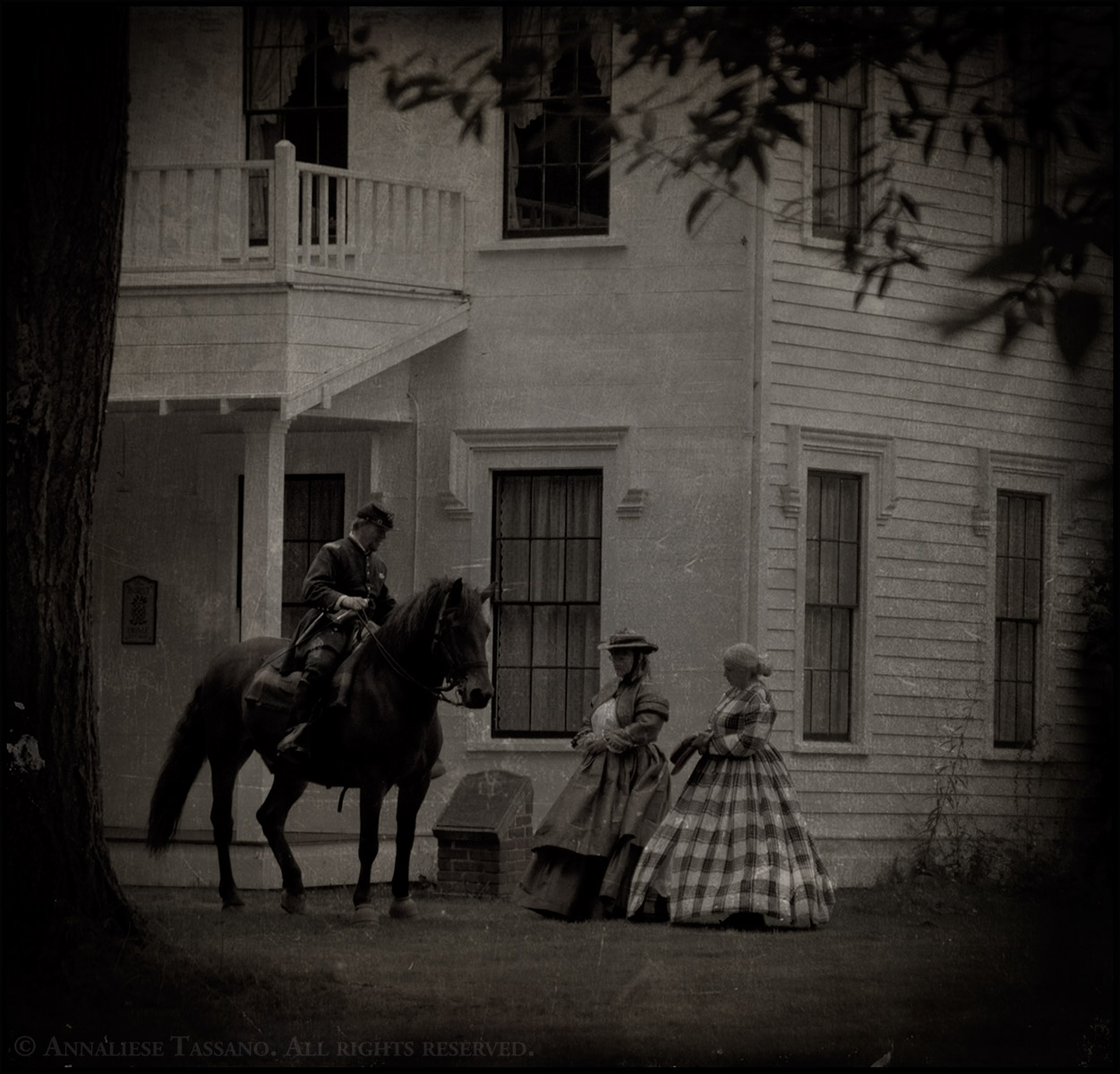 Civil War reenactors in Washington State, one man mounted on his Canadian Warmblood horse in his Union Cavalry uniform and two women standing on the ground in period dresses.