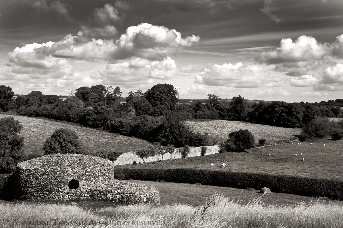 A stone folly behind New Grange in county Meath, Ireland, with sheep across the stone fence in the next field and fluffy white clouds in the sky.