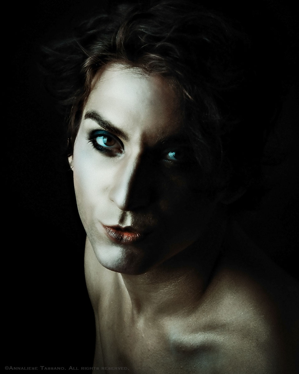 A handsome, young white man with theatrical make up looks at the camera from a dark background.
