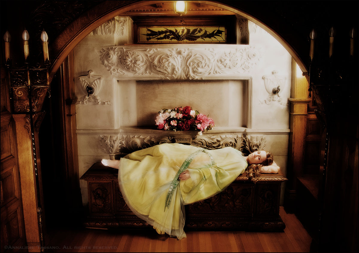 Sleeping beauty, with long blond hair and green and gold dress, lies sleeping in an ornate, wood panelled and carved stone atrium with a stained glass thistle above her.