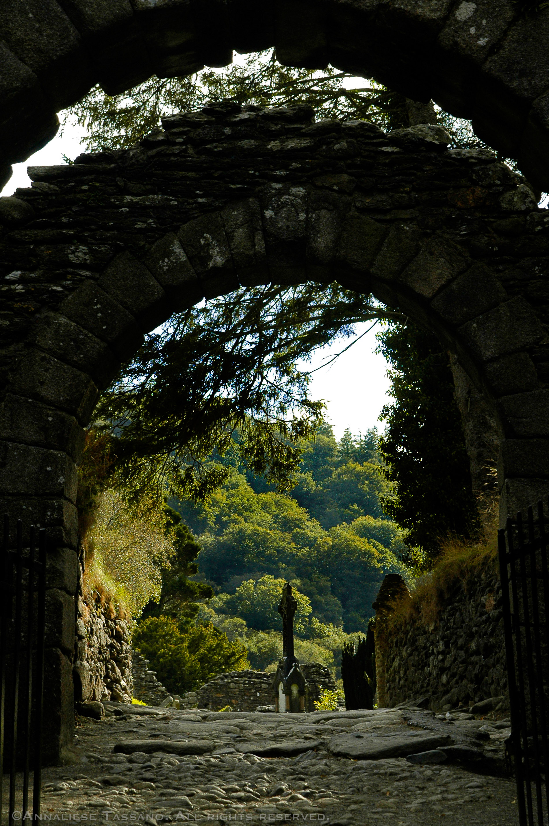 A hillside of green trees is seen in the sunshine beyond and ancient stone archway and cobblestone street in Glendalough, county Wicklow, Ireland.