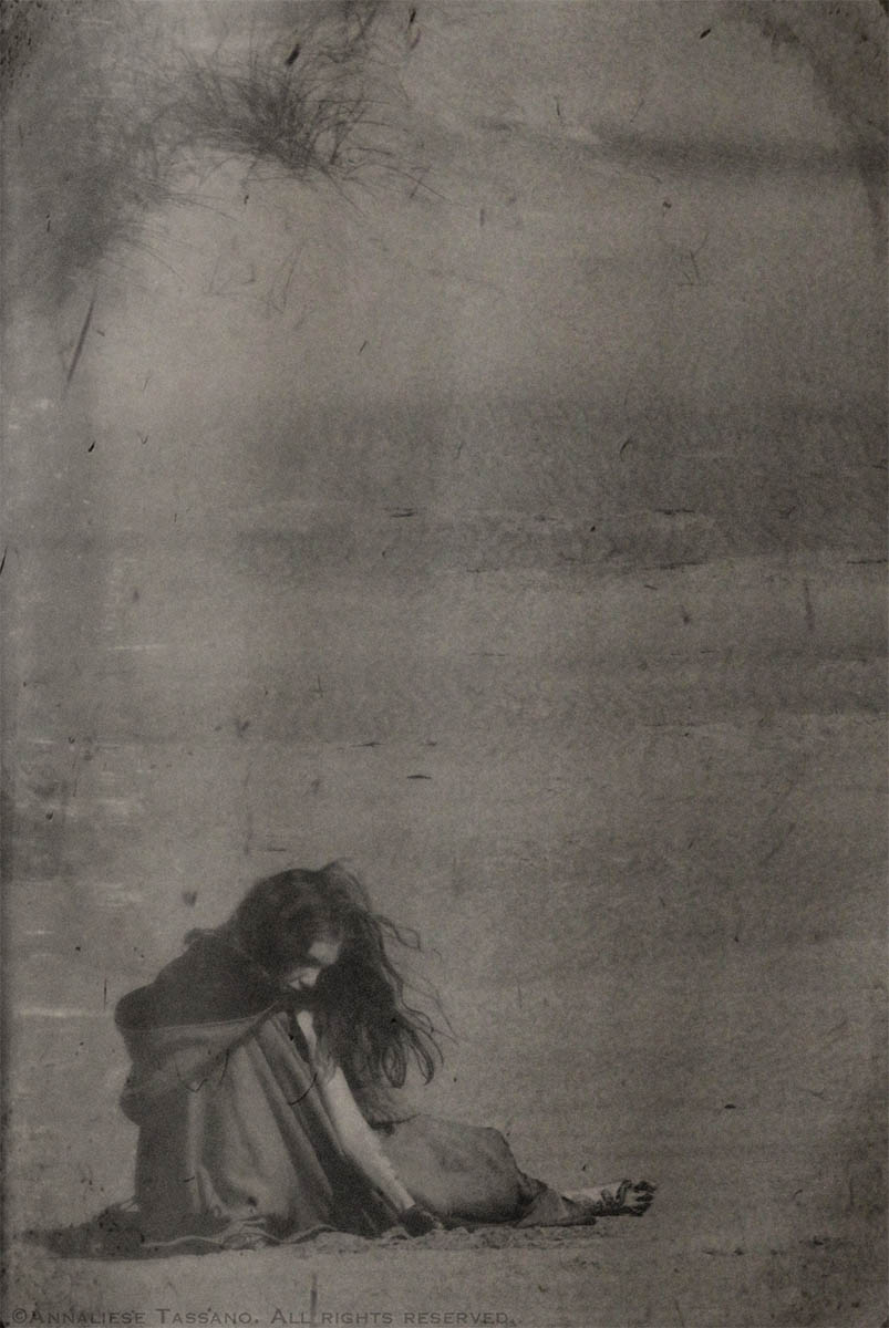 A young girl in a cloak sits on the beach playing in the sand in front of the dunes in the antique or vintage black and white photo.