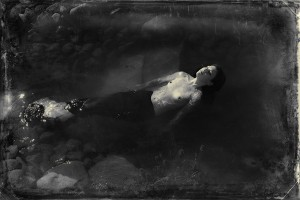 Seen in a victorian style photograph, a mermaid relaxes, floating in her pond.